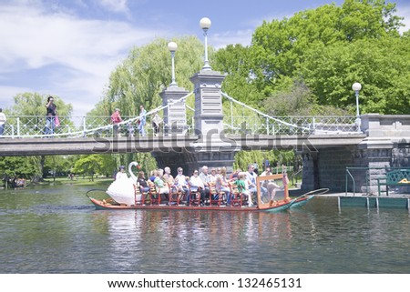 BOSTON - MAY 20: Swan boat with tourists goes by suspension bridge in Public Garden and Boston Common on May 20, 2010, Boston, MA.