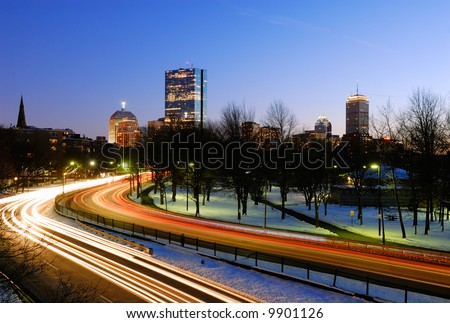 Boston skyline at dusk. Car lights on Storrow Drive lead to John Hancock building and Prudential Tower