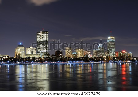 Boston skyline at night reflected on the frozen waters of Charles River