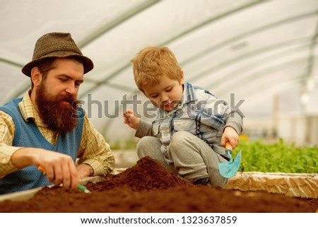 botanic worker. botanic worker child with father in greenhouse. farm worker in botanic garden. botanic worker in greenhouse farm. passionated about their job