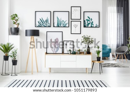 Botanical posters on the wall in a living room interior with white cabinet, wooden lamp and plants