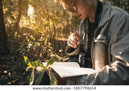 Botanists are taking note of the plants found in the tropical forests. Biologist researching in the forest. Botanist studying a newly flowering plant species. Photo stock ©