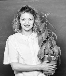 Botany education. Greenery benefits. Botany and nerd concept. Take good care plants. Botany and biology lesson. Botanical expert. Woman school teacher chalkboard background carry plant in pot.