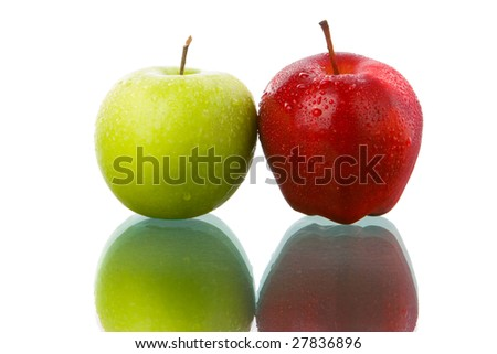 Both fresh red and green apple on glass table placed side by side.