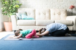 Both mother and daughter exercising together and doing yoga child's pose in the living room at home