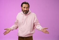 Bothered confused mature adult bearded man grey hair in pink hoodie arguing look pissed offended shrugging spread hands sideways dismay look clueless camera asking why, purple background