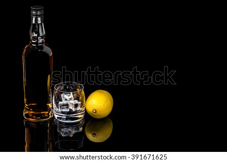 Bottle and a glass of whiskey with ice and  lemon on a black background #391671625