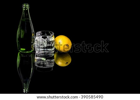 Bottle and glass beverage with ice and lemon on black background #390585490