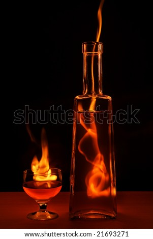 Bottle and glass in flame isolated on black background