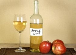 bottle and glass of home made apple wine with apples