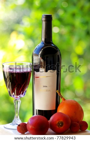 Bottle and glass of red wine and fruits.