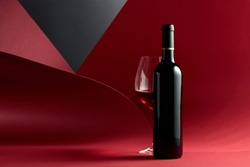 Bottle and glass of red wine. Copy space for your text.