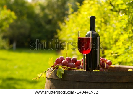 Bottle and glass of red wine with grapes on top of wooden barrel in vineyard