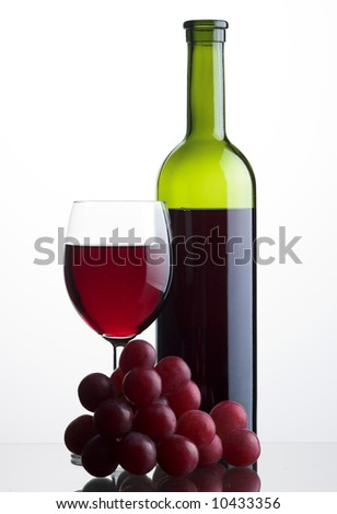 Bottle and glass of red wine with grapes on white backround