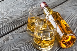 Bottle and glass of whiskey on a wooden background
