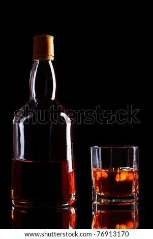 bottle and glass of whiskey on black background
