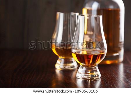 Bottle and glass of whisky spirit brandy on dark brown background ストックフォト ©