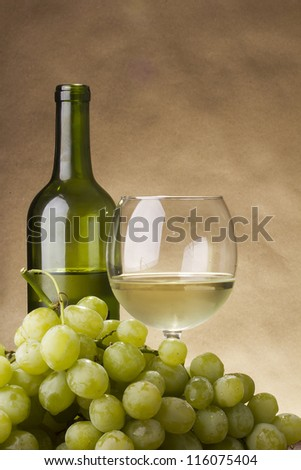Bottle and glass of white wine and a bunch of grapes.