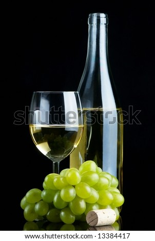 Bottle and glass of white wine with grapes and cork on black background