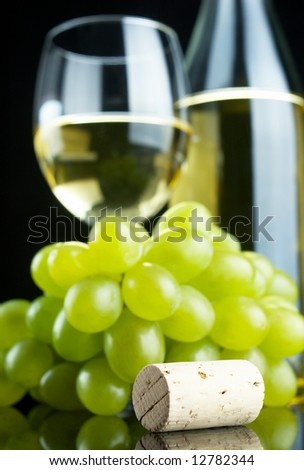 Bottle and glass of white wine with grapes and cork on black background, selective focus