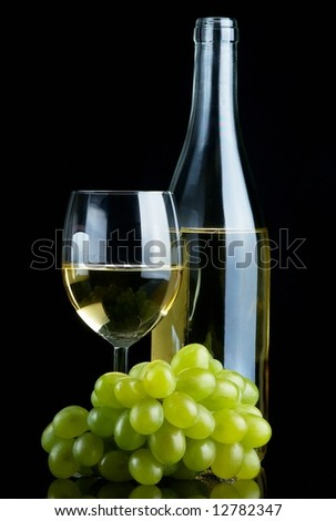 Bottle and glass of white wine with grapes on black background