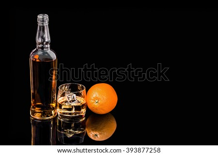 Bottle and  glass whiskey with ice and Orange on black background #393877258
