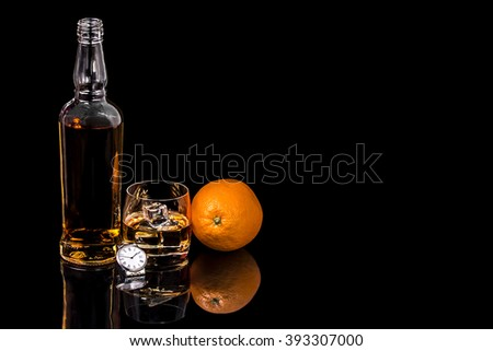 Bottle and glass whiskey with ice and wrist watch on black background #393307000