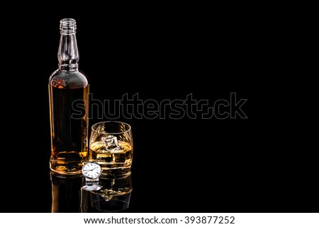 Bottle and glass whiskey with ice and wrist watch on black background #393877252