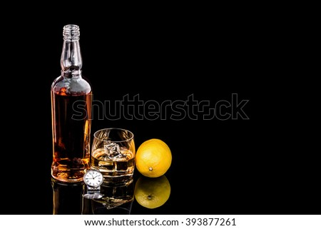 Bottle and glass whiskey with ice and wrist watch on black background #393877261