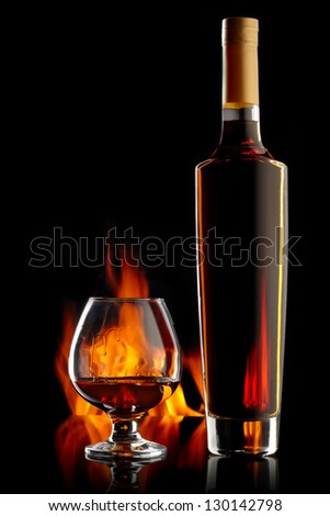 Bottle and glass with cognac over dark background with flame