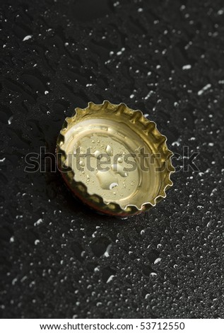 bottle cap with water droplets close up on black wet table background