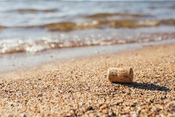 Bottle cork on the shore - trash after tourists - dirty beach