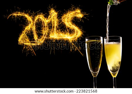 Bottle filling Champagne Glasses for celebrating new years eve 2015 with sparkling lightning numbers isolated on black background as new year greeting card