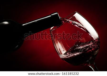 Bottle filling the glass of wine - splash of delicious flavor. #161185232