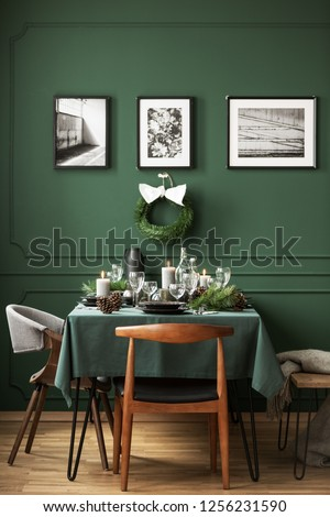 Bottle green dining room with table set for Christmas dinner