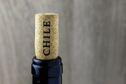 Bottle neck with a cork on a wooden background. Name of the wine country Chile is written on cork.