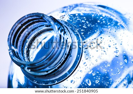 bottle neck with water drops on blue background