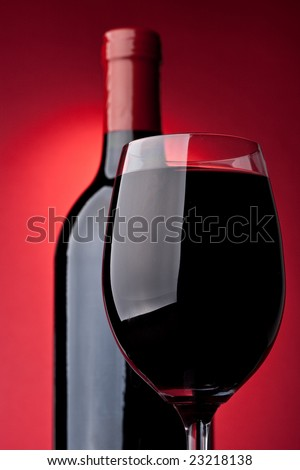 Bottle of a red vintage wine and glass on a red background