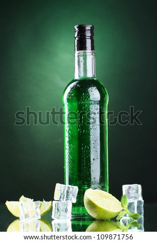bottle of absinthe with lime and ice on green background