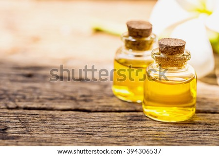 bottle of aroma essential oil or spa or natural fragrance oil with dry flower on wooden table, spa or alternative meditation aroma concept.