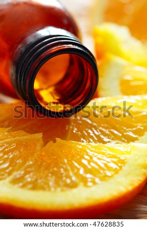 bottle of aromatic essence and fresh oranges