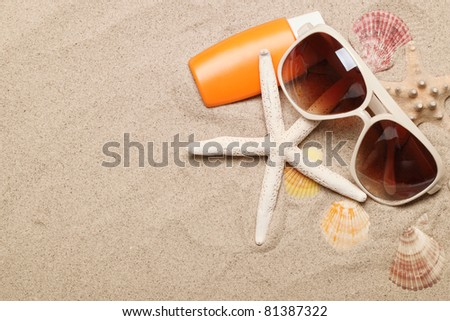 Bottle of balm solar with shells and sunglasses on sand