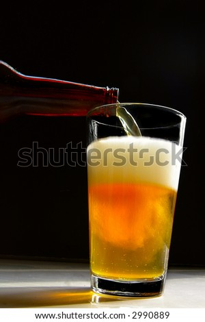 Bottle of beer being poured into a glass(slow shutter speed)