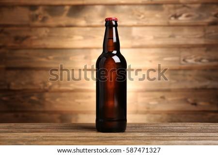 Bottle of beer on wooden background #587471327
