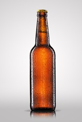 Bottle of beer with drops on gray background.