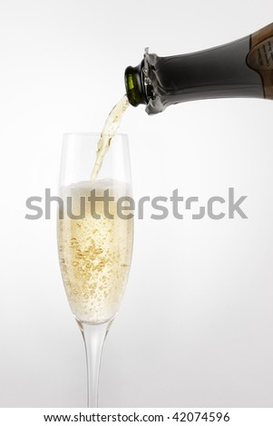 Bottle of bubbly champagne pours into flute