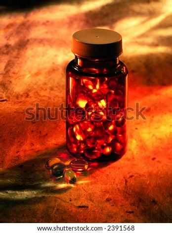 Bottle of capsules on warm mottles Background