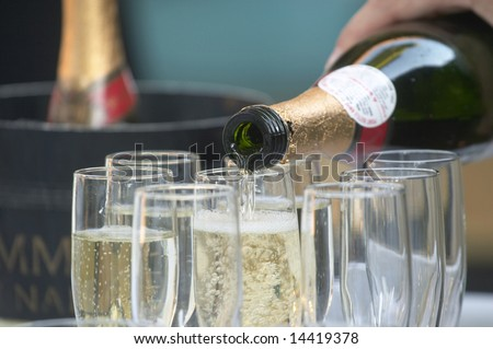 Bottle of champagne being poured into glasses