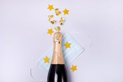Bottle of Champagne Gold Confetti in Shape of Star Protective Face Mask on Blue Background New Year 2021 Celebration Concept Top view Flat lay