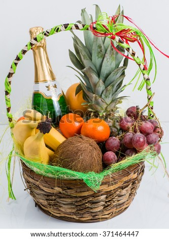 bottle of champagne in a basket of fruit on a light background